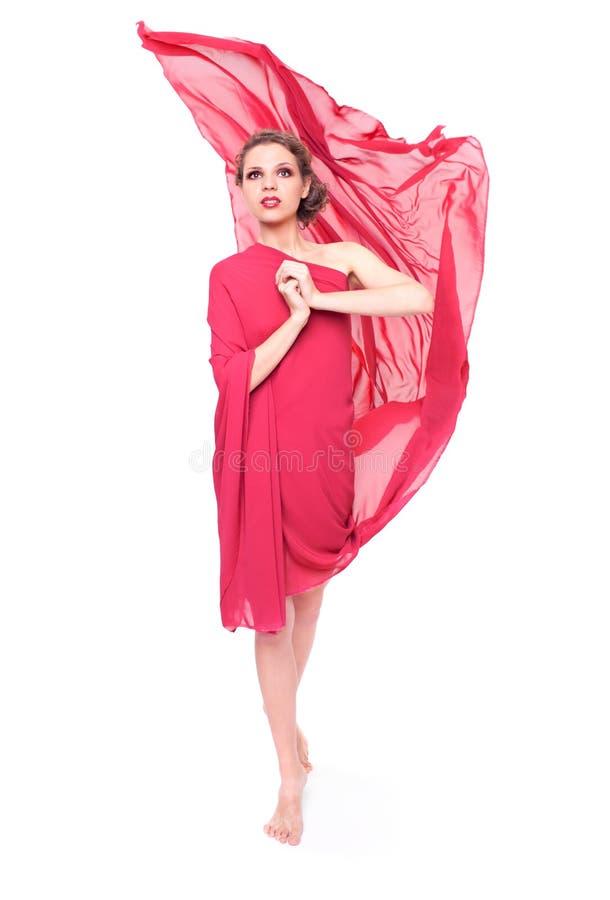 Mooie vrouw in rode vliegende kleding stock foto