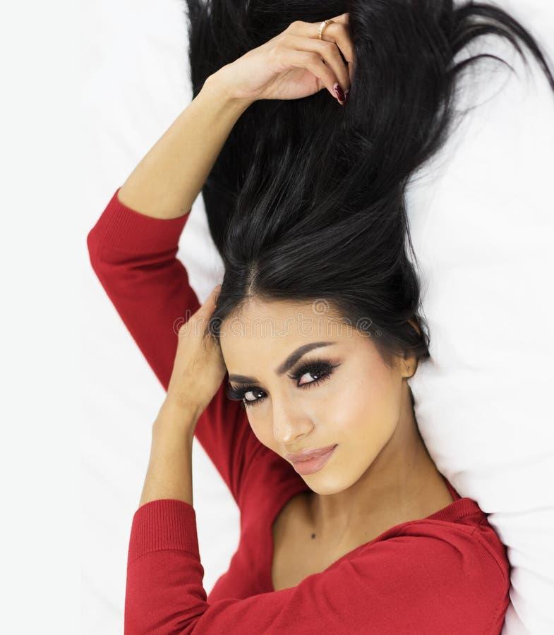 Mooie vrouw in rood met lang donker haar stock fotografie