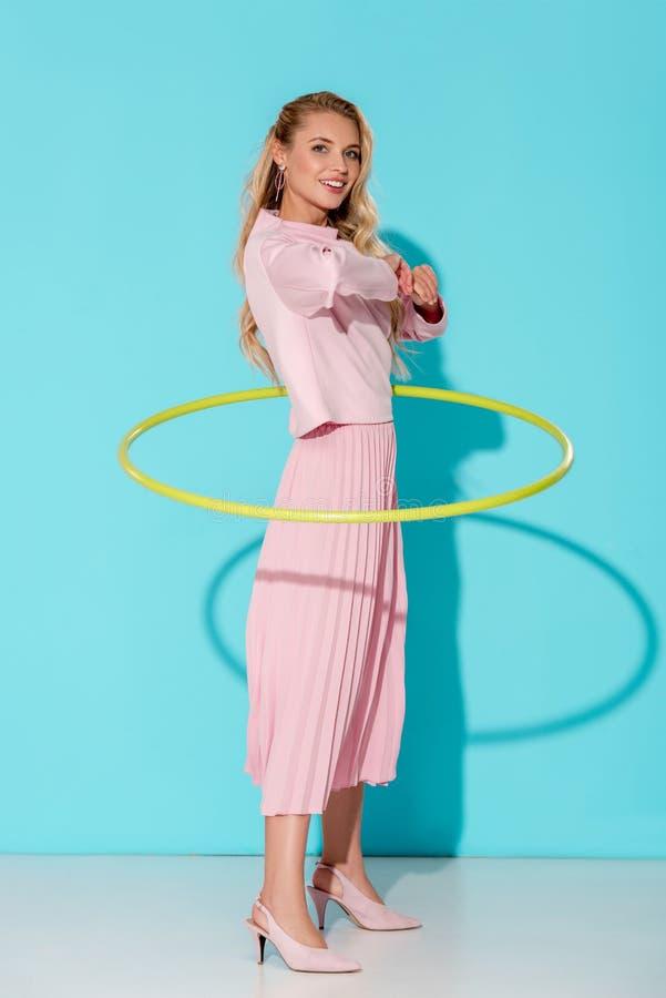 mooie vrouw in roze kleding die camera bekijken en met hulahoepel uitoefenen royalty-vrije stock foto