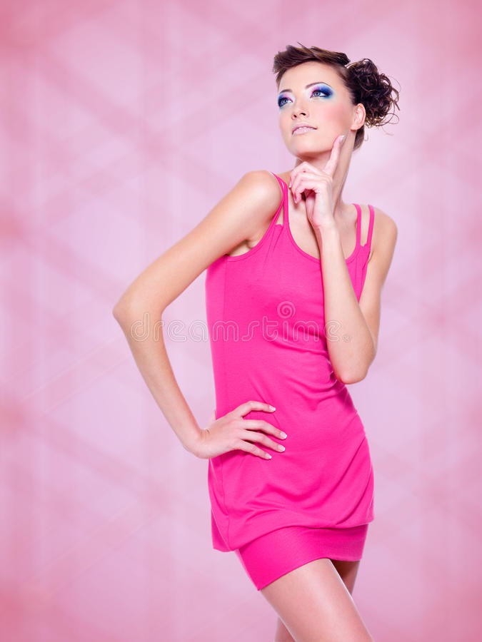 Mooie vrouw in roze kleding met maniermake-up stock foto