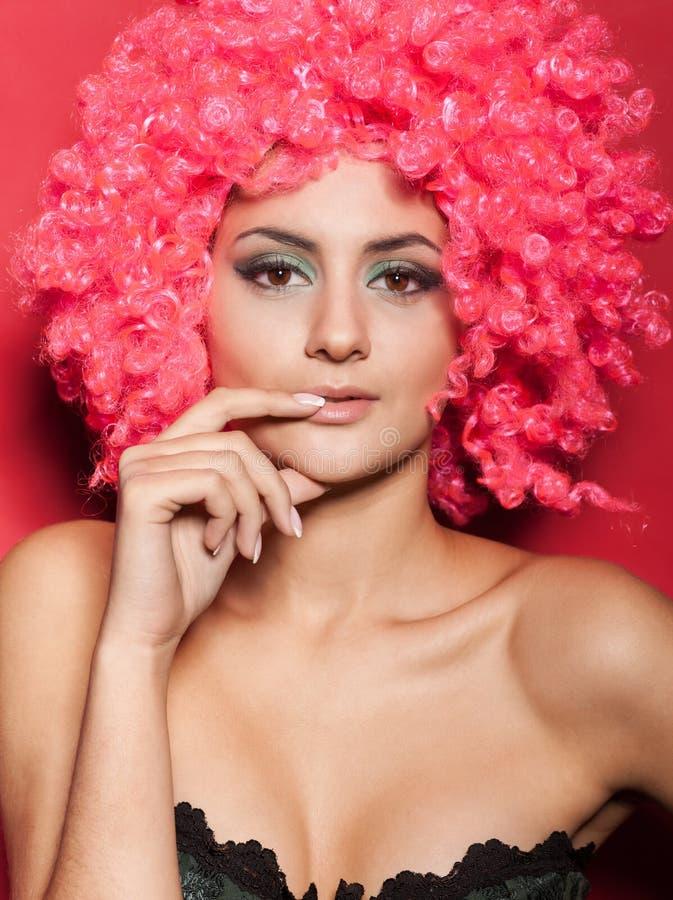 Mooie vrouw in roze pruik op rood stock afbeelding
