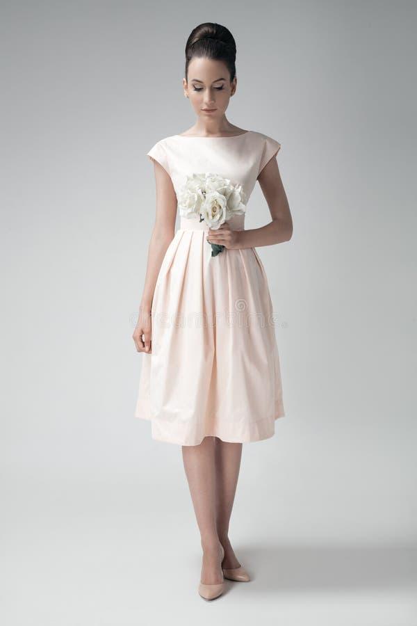 Mooie vrouw in roze retro kleding Witte rozen ter beschikking stock fotografie