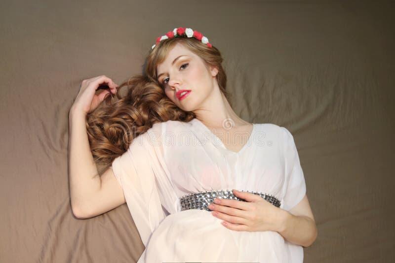 Mooie vrouw in rozenkroon en witte kleding royalty-vrije stock fotografie