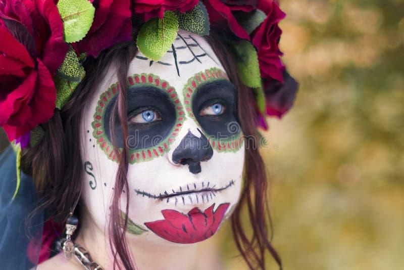 Mooie vrouw in schedel Katrina van make-up de traditionele Mexicaanse Calavera in het de herfstbos, in een kroon van rode bloemen royalty-vrije stock afbeeldingen