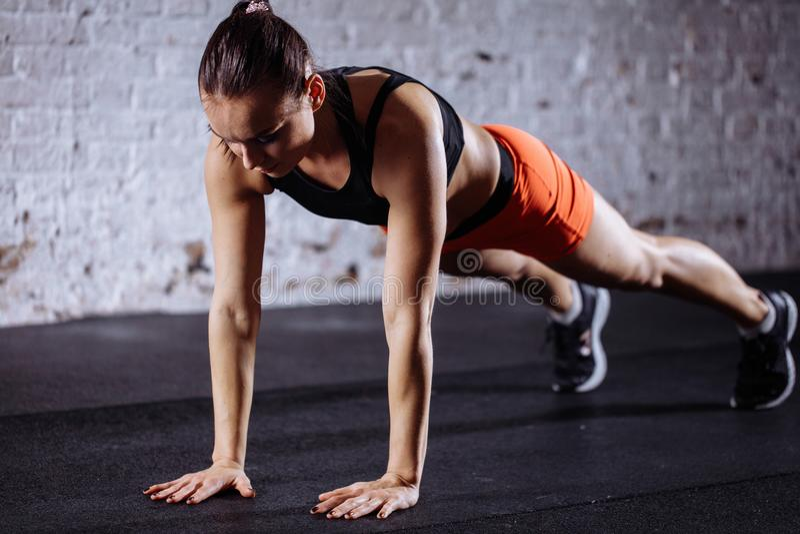 Mooie vrouw in sportkleding die plank doen terwijl trainnig bij dwars geschikte gymnastiek royalty-vrije stock foto