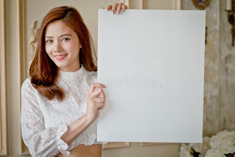 Mooie vrouw status, die witte lege reclame houden royalty-vrije stock fotografie