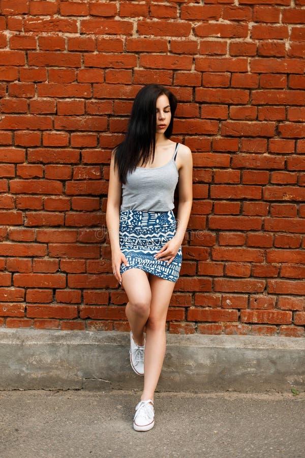 Mooie vrouw in tennisschoenen en een de zomerrok met een grijs overhemd stock foto