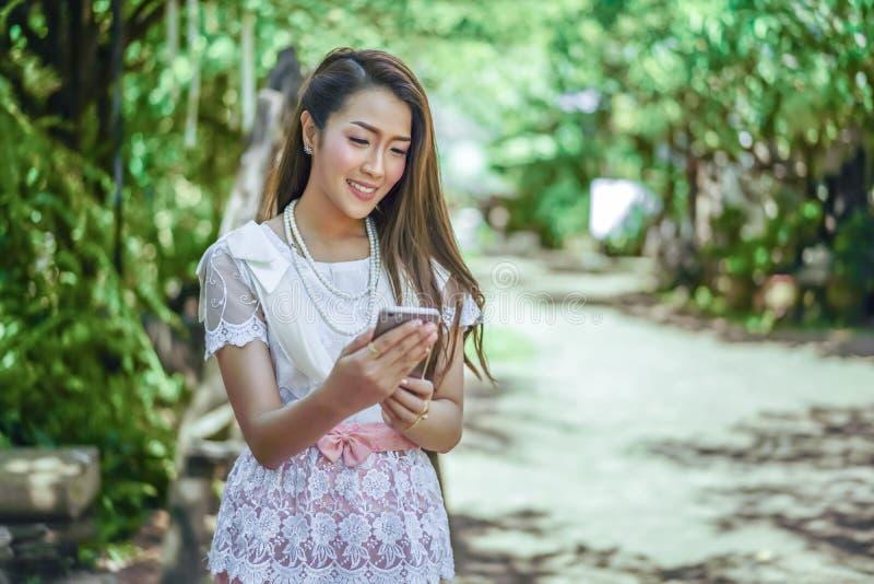 Mooie vrouw in Thaise traditionele kleding die smartphone gebruiken stock foto's