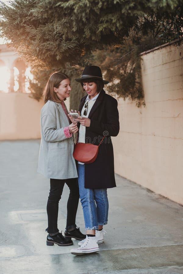mooie vrouw twee met toevallige kleding die bij zonsondergang glimlachen en mobiele telefoon met behulp van Achter Licht De achte royalty-vrije stock afbeelding