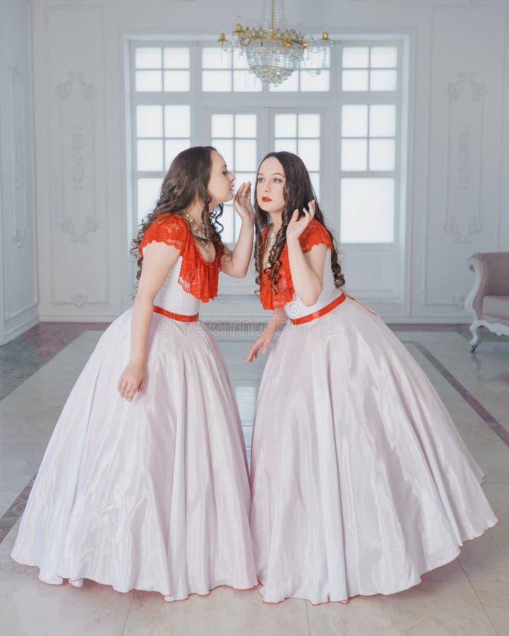 Mooie vrouw twee in middeleeuwse kleding met hoepelrokgefluister i royalty-vrije stock foto