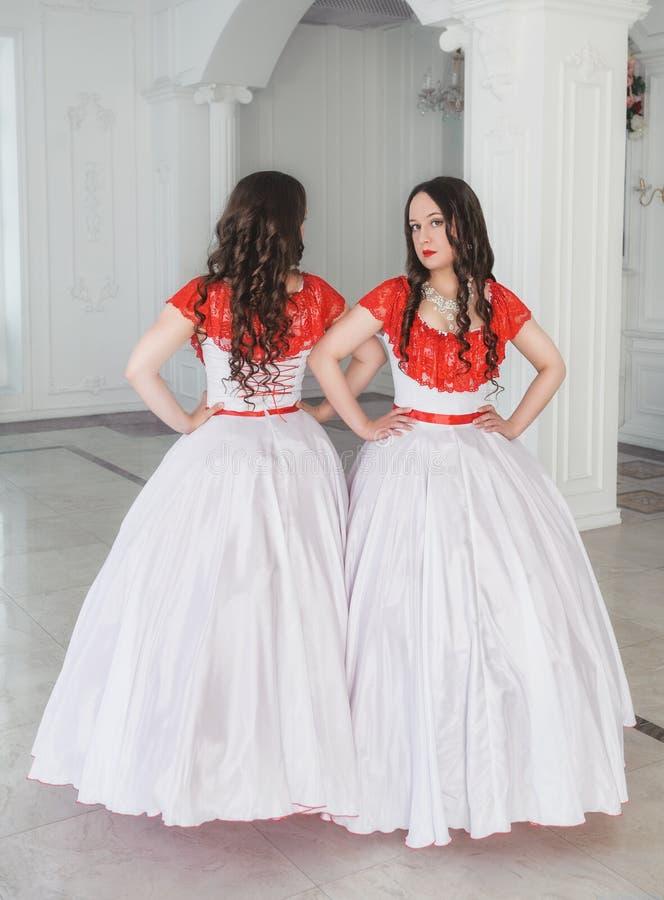 Mooie vrouw twee in witte en rode middeleeuwse kleding met crino stock afbeeldingen