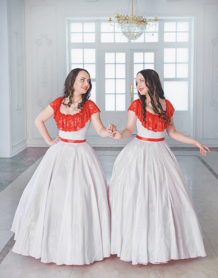 Mooie vrouw twee in witte en rode middeleeuwse kleding met crino stock foto's