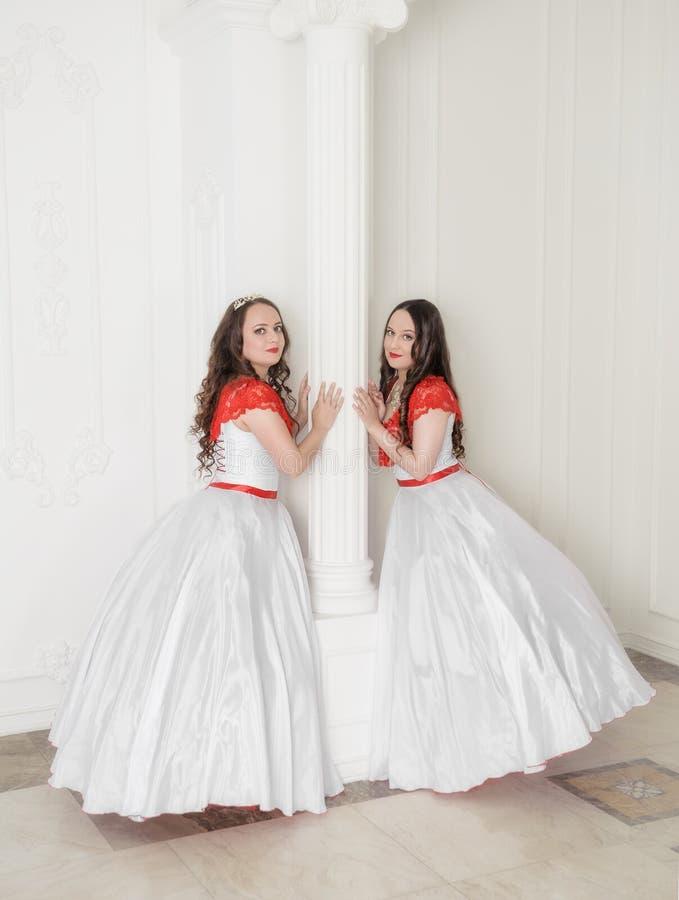 Mooie vrouw twee in witte en rode middeleeuwse kleding met crino royalty-vrije stock afbeelding