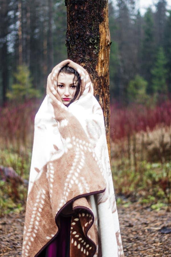 Mooie vrouw in warme deken in bos royalty-vrije stock foto's