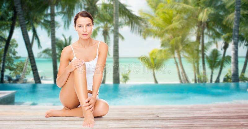 Mooie vrouw wat betreft haar benen over strand stock foto