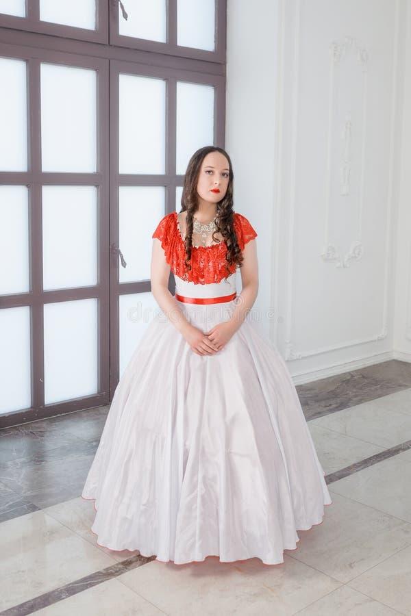 Mooie vrouw in witte en rode middeleeuwse kleding met hoepelrok royalty-vrije stock fotografie