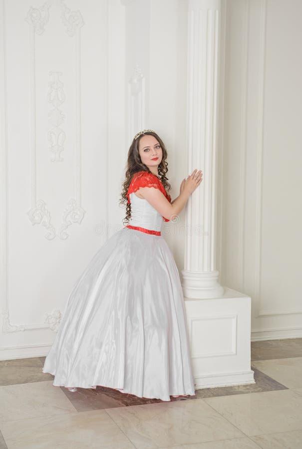 Mooie vrouw in witte en rode middeleeuwse kleding met hoepelrok royalty-vrije stock foto's