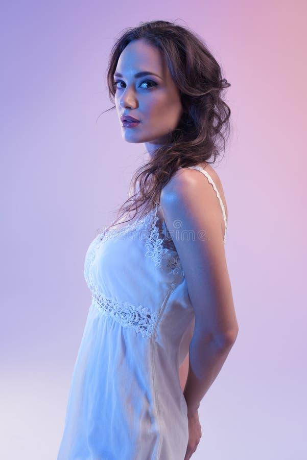 Mooie Vrouw in Witte Kleding en Blauw die Licht op Blauwe Achtergrond wordt geïsoleerd stock afbeelding