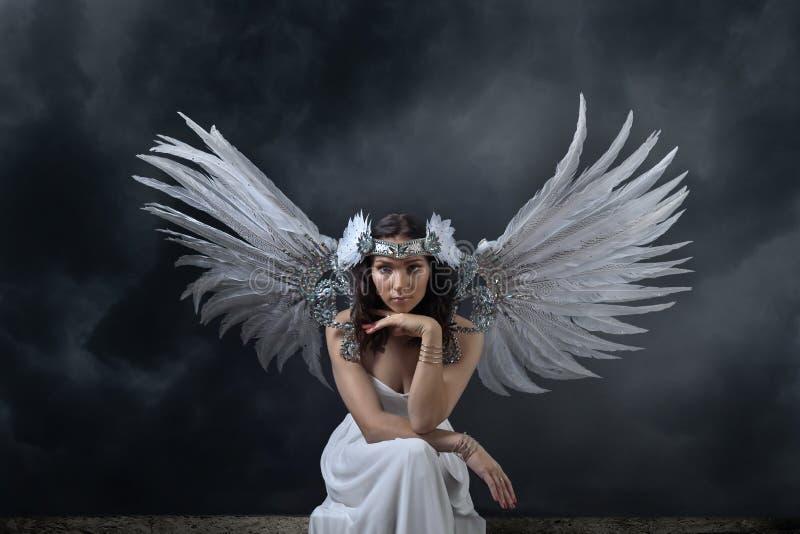 Mooie vrouw in witte kleding met engelenvleugels royalty-vrije stock afbeeldingen