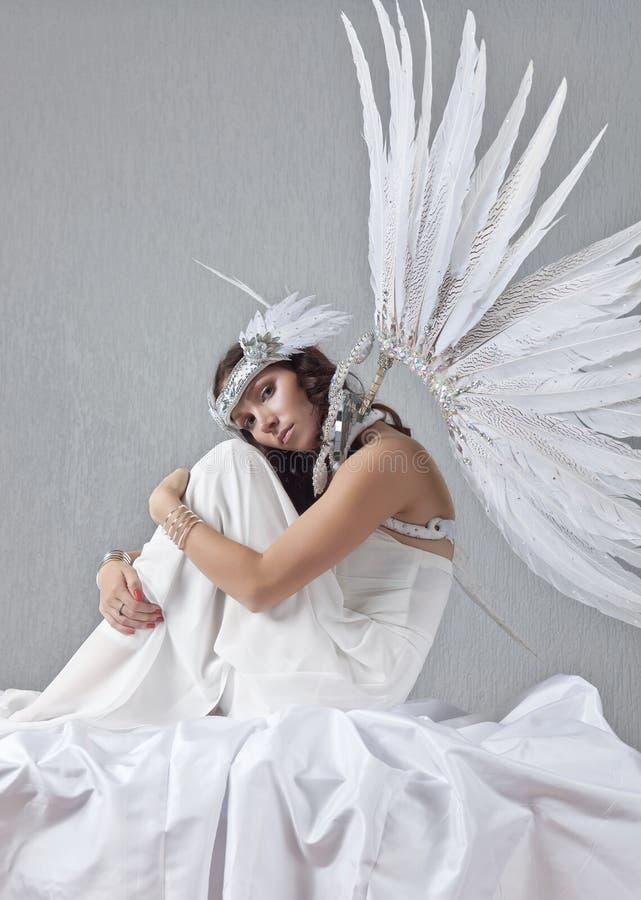 Mooie vrouw in witte kleding met engelenvleugels royalty-vrije stock afbeelding