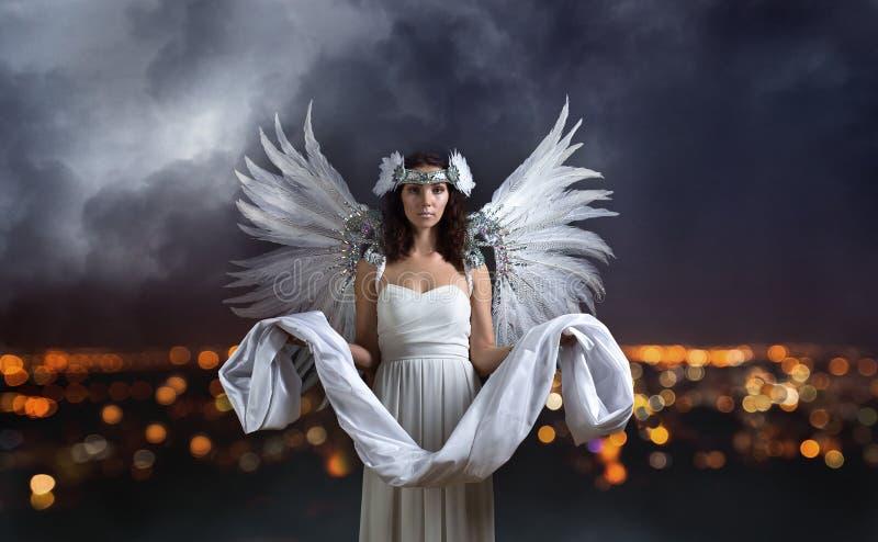 Mooie vrouw in witte kleding met engelenvleugels stock fotografie