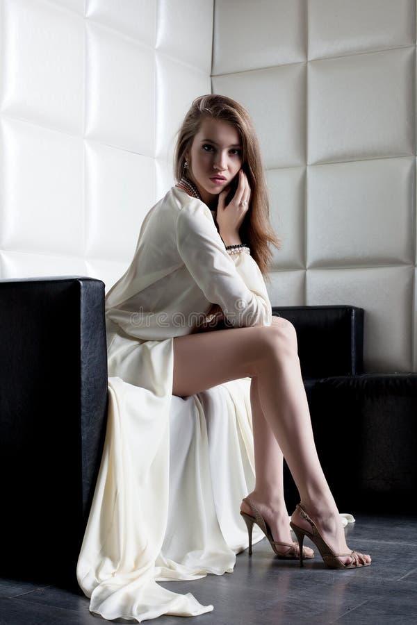 Mooie vrouw in witte kledingszitting op bank stock foto