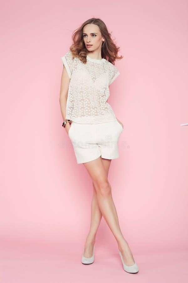 Mooie vrouw in witte kleren die op roze achtergrond stellen stock foto