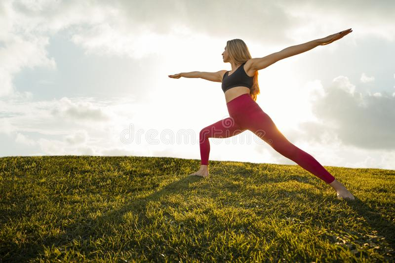 Mooie vrouw Yoga oefent Pose Warrior 2 Asana Position Tranquil Sunset - Silhouette Background stock afbeelding