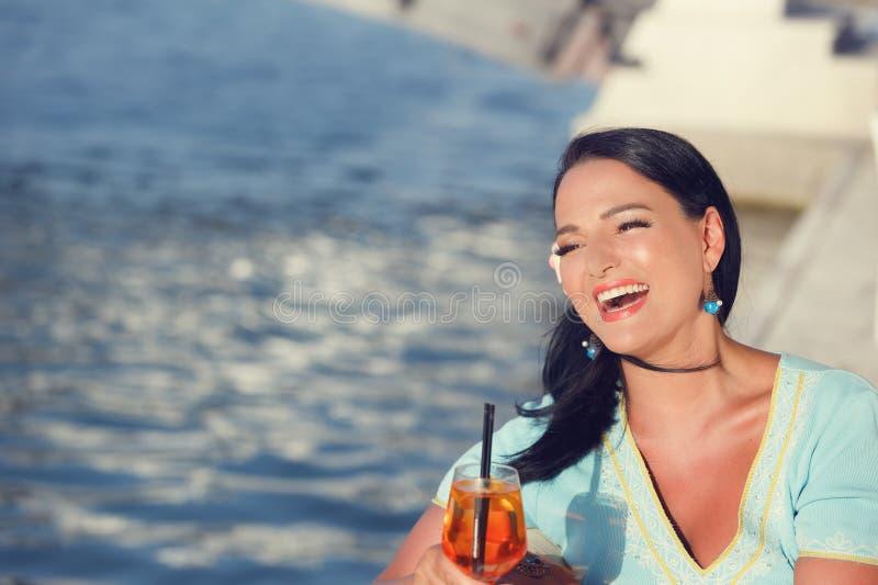 Mooie vrouw zitting en het drinken cocktail in openluchtkoffie stock foto