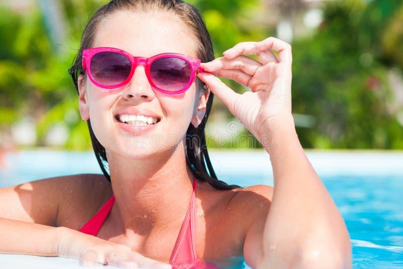 Mooie vrouw in zonnebril in de pool royalty-vrije stock foto