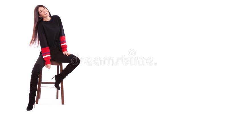 Mooie vrouw in zwart die kostuum op witte achtergrond wordt ge?soleerd Het leuke brunette zit op de stoel bij witte studio Sluit  royalty-vrije stock foto's