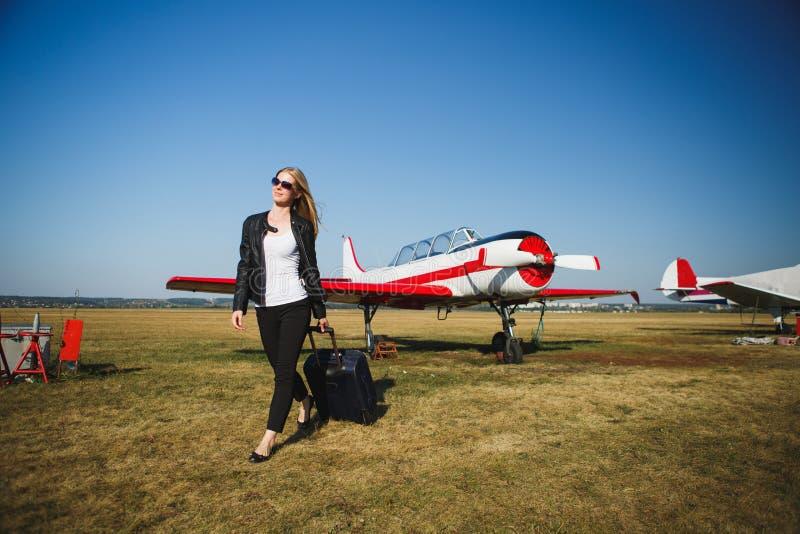 Mooie vrouw in zwart leerjasje die zich voor kleine uitstekende vliegtuigen bevinden royalty-vrije stock fotografie