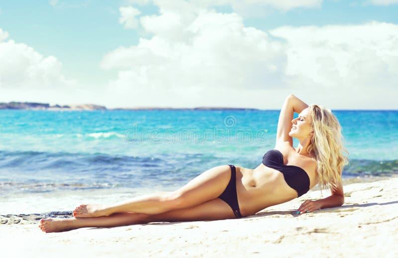 Mooie vrouw in zwarte bikini Jong en sportief meisje die stellen royalty-vrije stock afbeelding