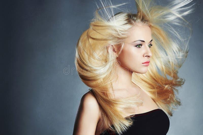 Mooie vrouw in zwarte kleding Sexy Blond meisje Gezond haar De salon van de schoonheid Vliegend haar stock foto's