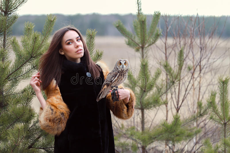 Mooie vrouw in zwarte laag met een uil op zijn wapen Donkerbruin w royalty-vrije stock fotografie