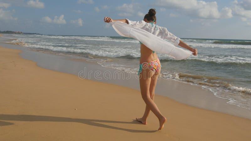 Mooie vrouw in zwempak en overhemd die op overzees strand blootvoets en opgeheven handen lopen Jong meisje die op de oceaan gaan royalty-vrije stock afbeeldingen