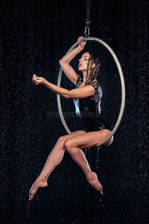 Mooie vrouwelijke acrobaatzitting in luchthoepel onder regen op zwarte achtergrond stock foto