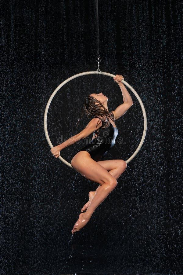 Mooie vrouwelijke acrobaatzitting in luchthoepel onder regen op zwarte achtergrond stock foto's
