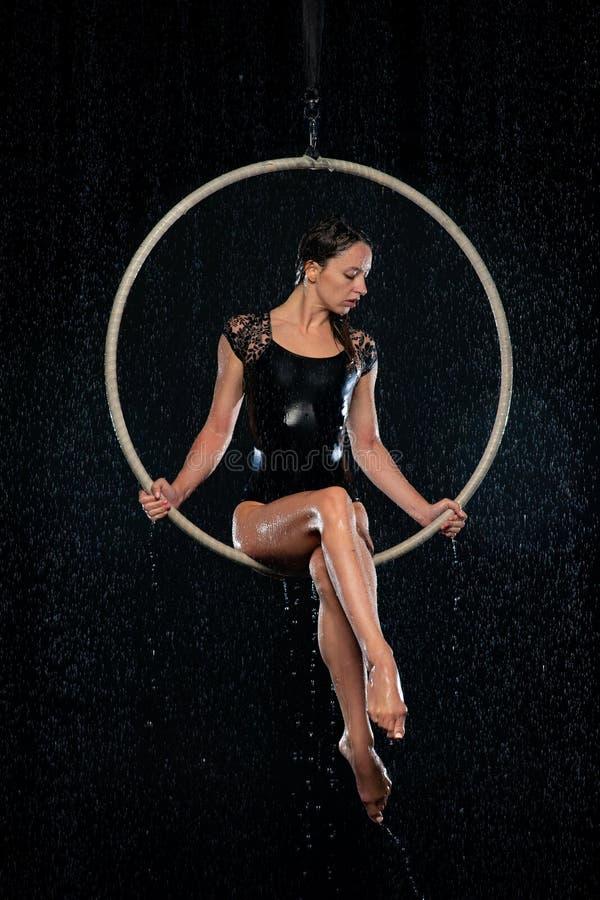 Mooie vrouwelijke acrobaatzitting in luchthoepel onder regen op zwarte achtergrond royalty-vrije stock foto's