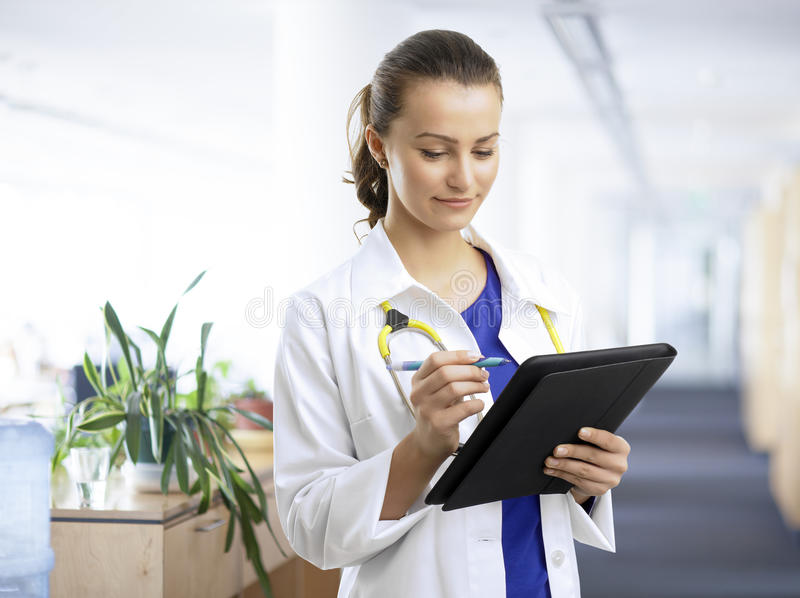 Mooie vrouwelijke arts die de geduldige grafiek onderzoeken stock foto