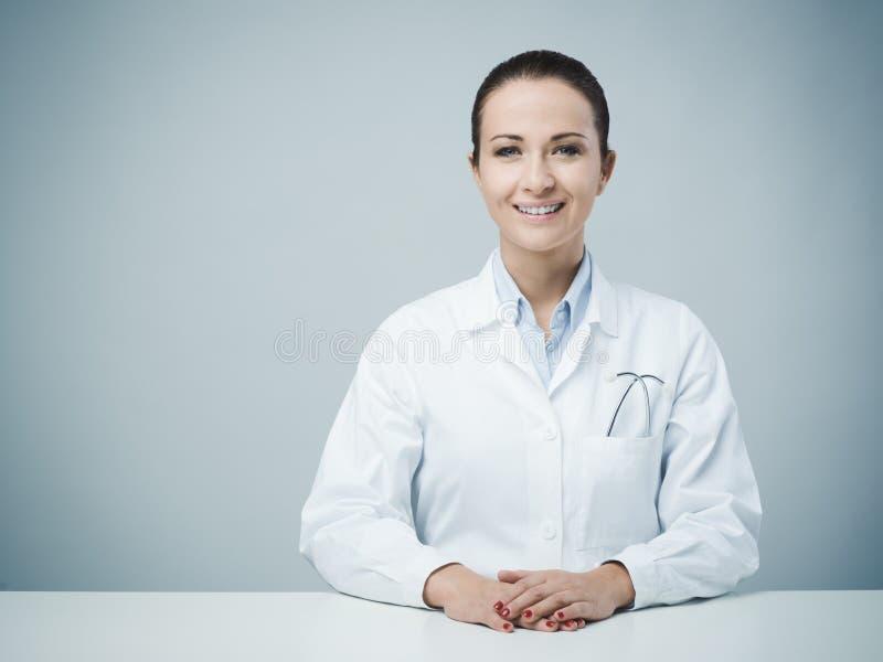 Mooie vrouwelijke artsenzitting bij bureau stock foto