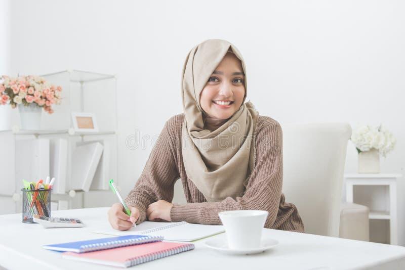 Mooie vrouwelijke Aziatische student met hijab die thuiswerk doen stock foto's