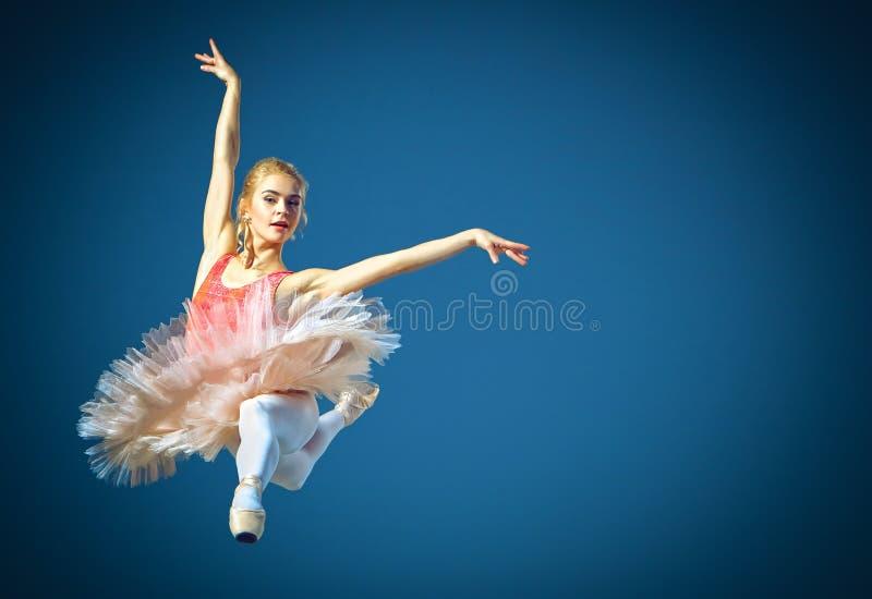 Mooie vrouwelijke balletdanser op een grijze achtergrond De ballerina draagt roze tutu en pointe schoenen stock afbeelding