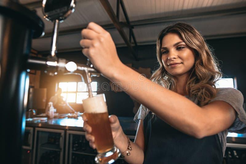 Mooie vrouwelijke barman die bier in bar onttrekken royalty-vrije stock afbeelding