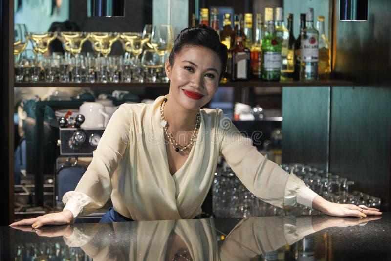 Mooie vrouwelijke barman status ontspannen bij teller stock afbeeldingen