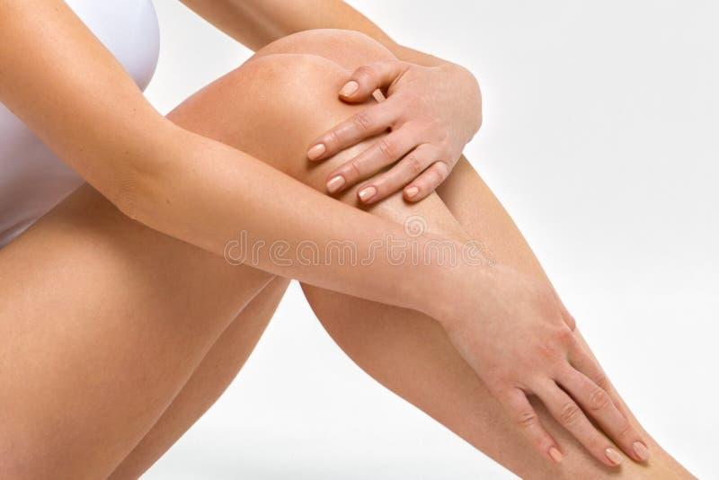 Mooie vrouwelijke benen Een vrouw koestert haar knieën De foto's in de studio sluiten omhoog royalty-vrije stock afbeelding