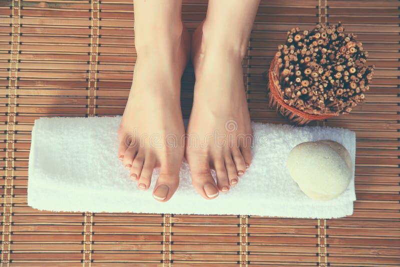 Mooie vrouwelijke benen op handdoek, houten vloerachtergrond royalty-vrije stock fotografie