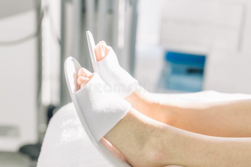 Mooie vrouwelijke benen in witte pantoffels royalty-vrije stock afbeelding
