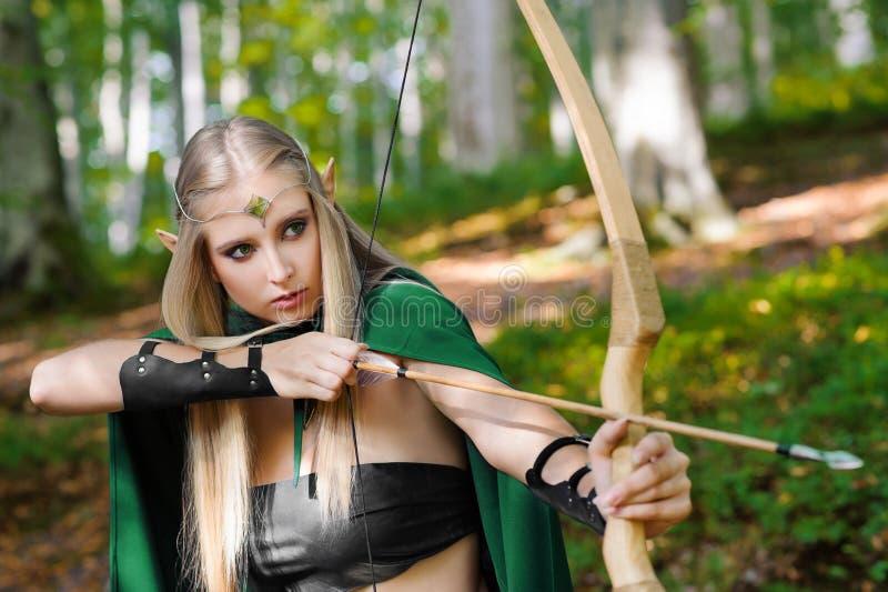 Mooie vrouwelijke elfschutter in de bos jacht met een boog royalty-vrije stock afbeelding