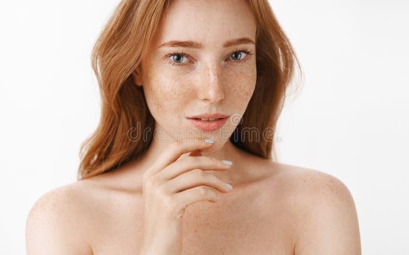 Mooie vrouwelijke en aantrekkelijke vrouw met natuurlijke rode haar en sproeten op gezicht en lichaam wat betreft kin zacht met royalty-vrije stock foto's